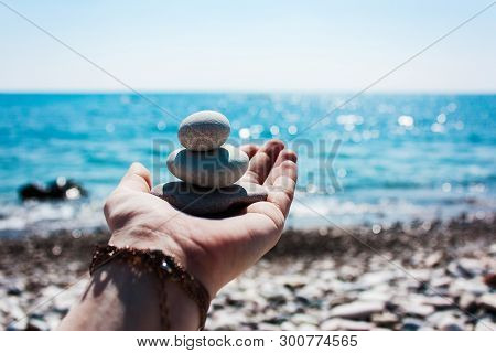 Balance Of Stones On The Hand Against The Background Of The Sea.