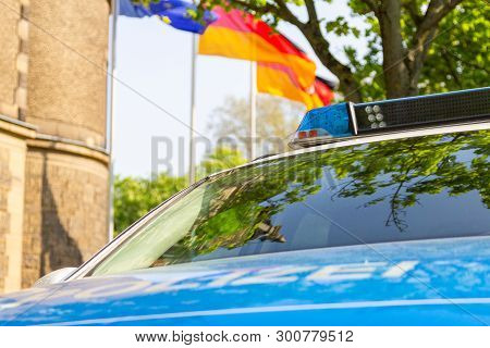 German Police Car Stands In Front Of A Police Department. The German Word Polizei Means Police.