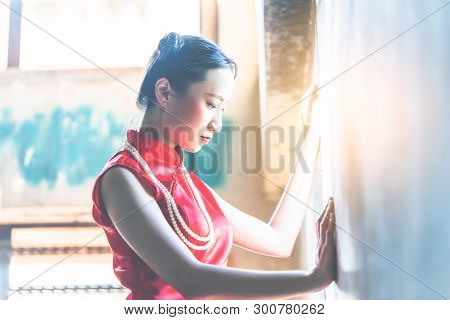 Lonely Chinese Woman Is Looking Out The Light On The Windows With Sadness