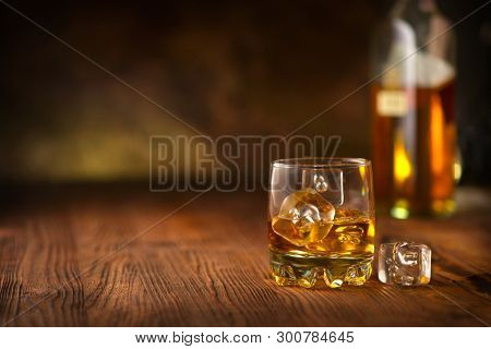 Whiskey with ice cubes. Glass of Whisky and the bottle on wooden table over dark background. Glass of rum alcohol close-up.