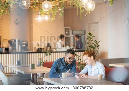 Contemporary teenage couple sitting by table in cafe, having coffee and searching in the net for curious videos
