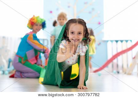 Children Kids Playing With Clown On Birthday Party In Entertainment Centre. Child Girl Climbing Thro