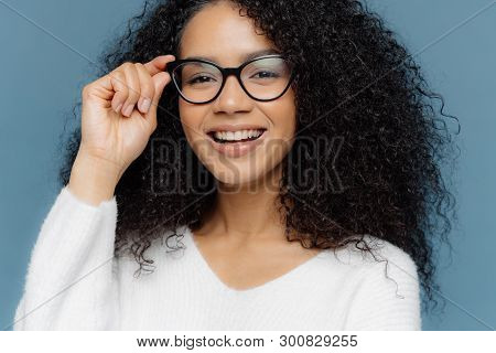 Cropped Shot Of Good Looking Woman Wears Optical Glasses, Smiles Broadly, Shows White Perfect Teeth,