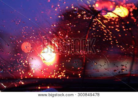 Traffic Is Viewed Through The Car's Windshield Covered In Rain, . Beautiful Background Of Rain And L