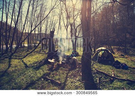 Tourists In A Hiking To Halt Food Cooked On The Campfire. Group In Camp