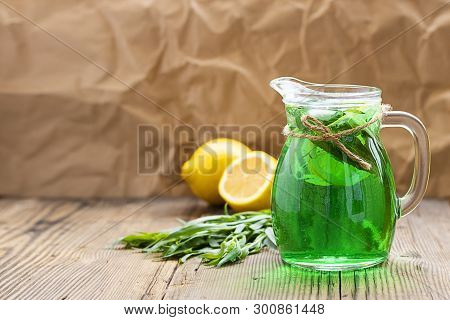 Summer Cold Green Drink Made From Tarragon, With Mint And Slices Lemon In Glass Decanter In Focus An