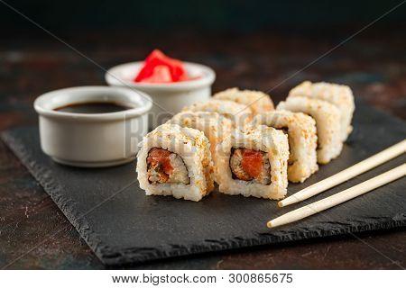 Japanese Sushi Rolls Served On Stone Slate On Dark Background. Sushi Rolls, Maki, Pickled Ginger And