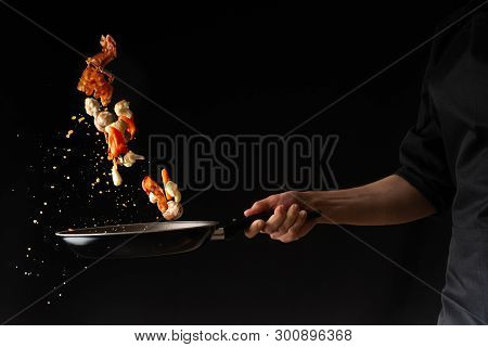 Cook Prepares Bacon Pieces With Garlic And Hot Pepper In A Pan, Freeze In The Air, On A Black Backgr