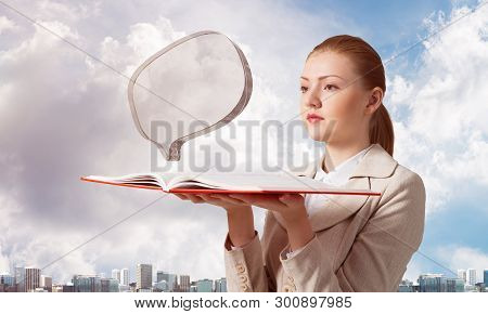 Woman Looks At Transparent Speech Bubble Above Opened Notebook. Business Communication And Conversat