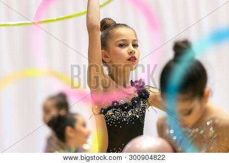 Portrait of a little pretty girl trying to win the rhythmic gymnastics championship, dancing with a hoop and wearing beautiful leotard embroidered with rhinestones poster