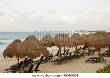 Chaise Lounges Under Straw Thatched Umbrellas On A Tropical Beach