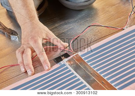 Installation infrared carbon heating film for floor. Layout and connection of heating elements with each other. Connecting wiring with contact clip. Electrical floor heating system, radiant heating