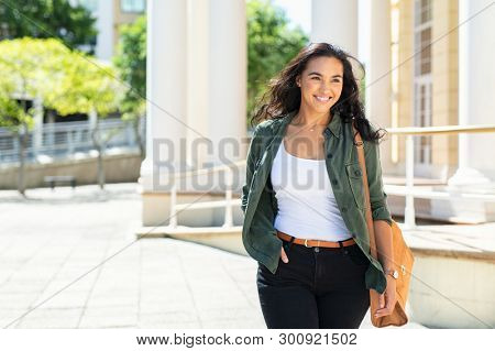 Pretty casual natural woman walking in urban street and looking away. Cheerful latin girl with bag travelling across the city. Beautiful young woman smiling outdoor.