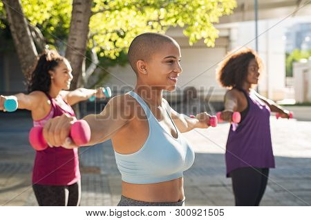 Group of curvy women in training session of aerobics using dumbbells at park. Bald woman doing exercise with other people in background. Team oversize girls using fitness weights outdoor at sunset.