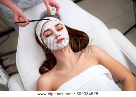 Hands Of Cosmetology Specialist Applying Facial Mask Using Brush, Making Skin Hydrated And Healthy.