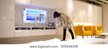 Paris, France - Apr 12, 2016: Woman Testing The Furniture At The Ikea Furniture Market Living Room W