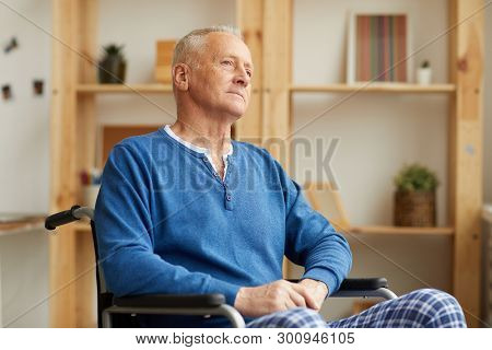 Warm Toned Portrait Of Pensive Senior Man Sitting In Wheelchair At Home And Looking Away, Copy Space