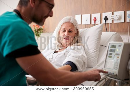 Male Nurse Taking Mature Female Patients Blood Pressure In Hospital Bed With Automated Machine