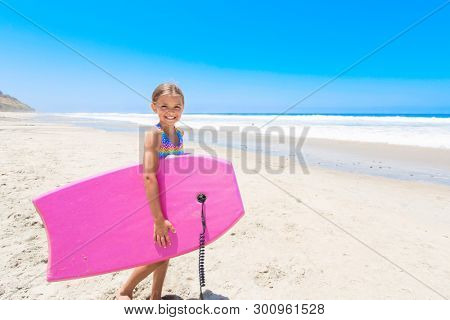 Cute little girl playing in the ocean during her summer vacation. Fun summer lifestyle photo with lots of copy space