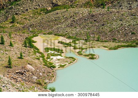 Lake Of Old Turquoise Color Near Stone Slope Of Mountain With Bog Terrain. Smooth Surface Of Water O