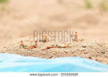 Miniature People Wearing Swimsuit Relaxing On The Beach