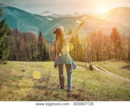 Young aviator girl with her airplane toy starting fly. Beautiful spreeng mountains view at sunny day. Travell, jorney, Aviation, Flying, freedom, holidays concept.