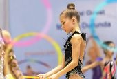 Beautiful little gymnast in the competition dressed in gorgeous black leotard performs an acrobatic moves with a hoop, rhythmic gymnastics school poster