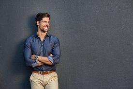 Happy successful businessman in smart casual looking away. Portrait of satisfied business man with crossed arms isolated over grey background. copy space. Handsome young man smiling against grey wall.
