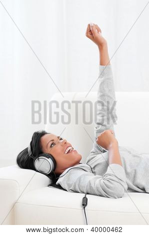 Joyful beautiful woman listening music and having fun on sofa at home