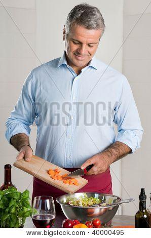 Happy mature man preparing an healthy vegetarian salad at home