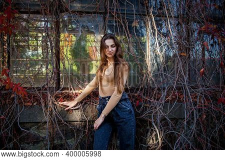 A Girl With Long Hair In A Bodysuit And Jeans Posing In An Autumn Park Against The Background Of A W
