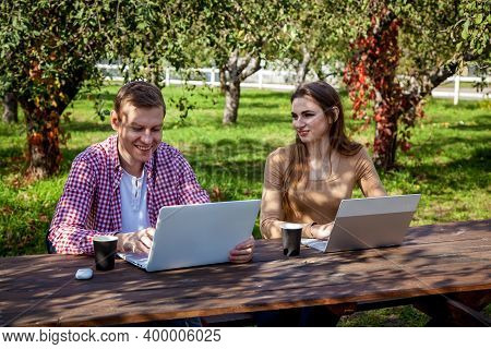 A Young Couple Spends Time Together In The Park, Studies And Works While Sitting Near A Tree With A