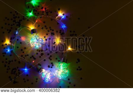 Christmas Glowing Garlands In The Form Of Light Bulbs On A Dark Background. New Year Composition, Ch