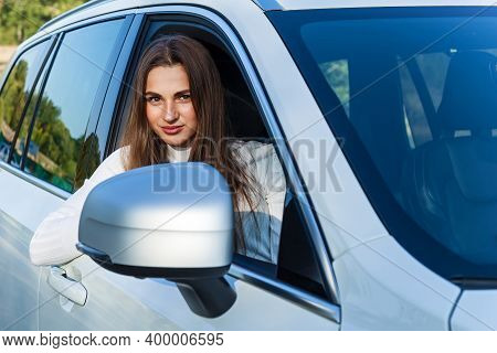 Happy Girl Looks Out The Window Of A White Car And Smiles