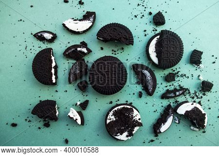 Delicious Sandwich Cookies With Chocolate Chips And Cream On A Green Background, Flat Lay. Chocolate