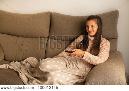 Woman Lying On The Sofa And Covered With A Blanket Looks At The Television With A Smile And Changes