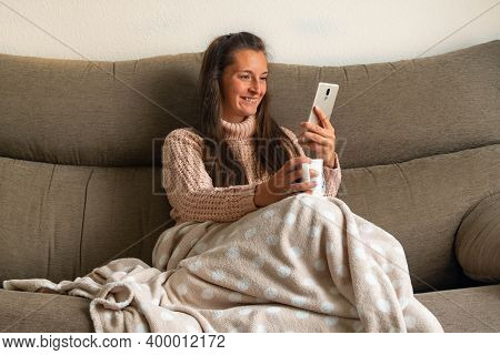 Happy Woman Sitting On A Sofa Holds Her Mobile With One Hand While Making A Video Call Or Checking T