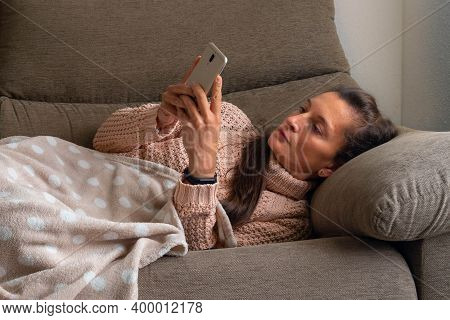 Smiling And Happy Woman, Sitting On A Sofa And Covered With A Blanket Greets While Making A Video Ca
