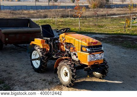 Small Mini Red Modern Orange New Tractor With Trailer Standing Near Hangar Building At Farm Countrys