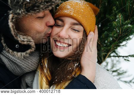 Man Kissing His Woman In A Cheek In Front Of A Fir Tree In The Winter.