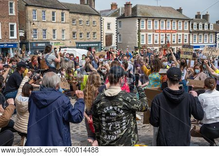 Richmond, North Yorkshire, Uk - June 14, 2020: A Group Of Black Lives Matter Protesters Kneel With T