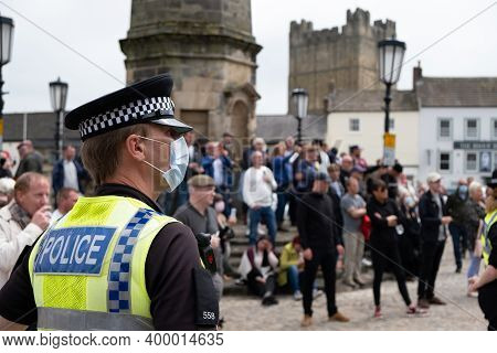 Richmond, North Yorkshire, Uk - June 14, 2020: A Police Officer Wearing A Face Mask Watches Proteste