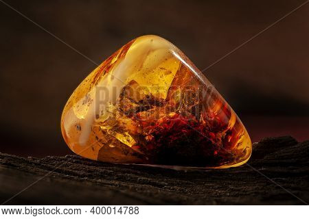 Beauty Of Natural Raw Amber. A Piece Of Yellow-red Transparent Natural Amber With Inclusions In It.