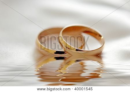 Two wedding rings with white flower in the background, wedding photo