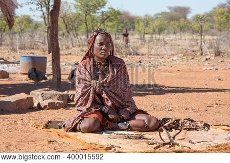 Namibia, Africa, Himba Village, July 18, 2019:. Himba Tribe Woman In Traditional Dress Sits On The G