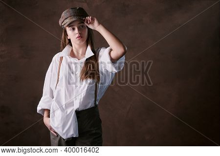 Girl Teenager In A Hat With A Visor In A White Shirt And Trousers. Studio Brown Background, Fashion