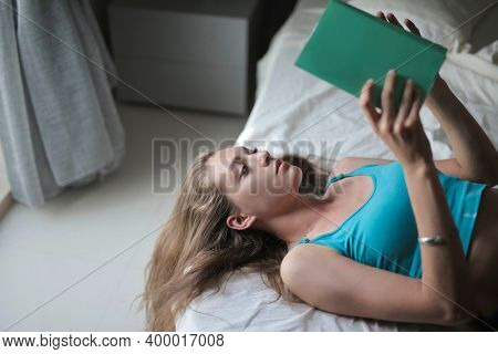 woman reads a book lying on a bed