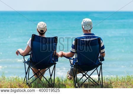 Family Man And Woman Relax And Unwind In Camping Chairs On The Seashore