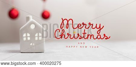 Merry Christmas And Happy Holidays Composition. Small Toy Model House And Red Balls On White Horizon