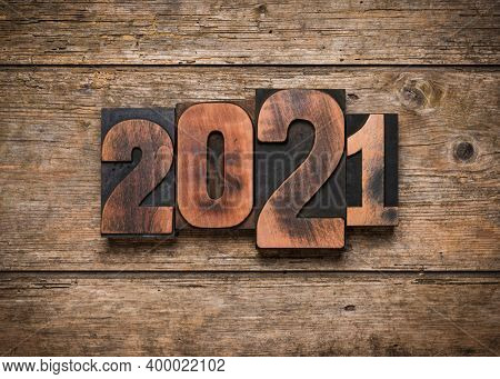 Year 2021 set with vintage wooden letterpress printing block numbers on rustic planks background
